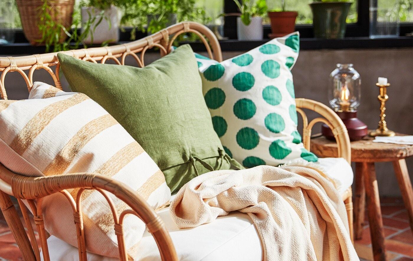 Trois oreillers de couleurs et de motifs différents, sur un canapé en rotin naturel dans un salon.