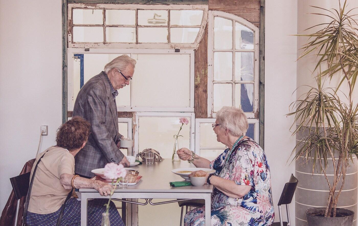 Trois personnes âgées mangeant autour d'une table