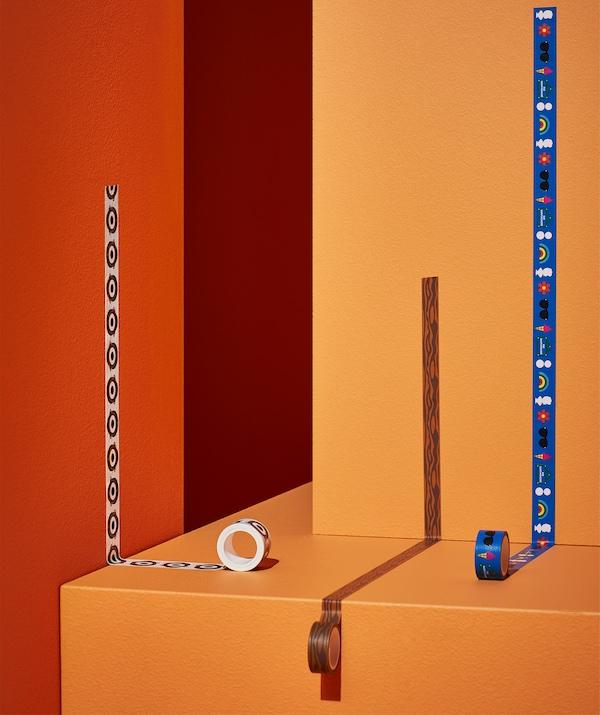 Trois rouleaux de ruban adhésif en papier Washi à motifs variés présentés dans une déco orange et rouge.