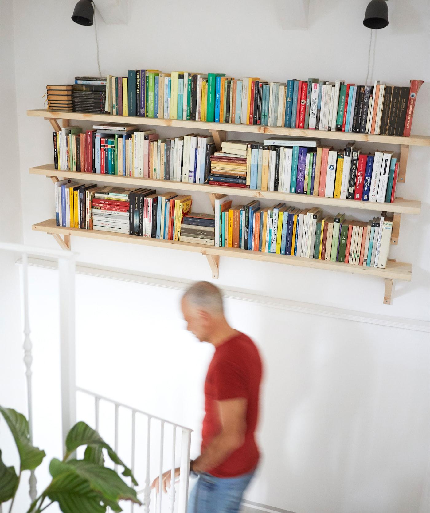 Trois tablettes remplies de livres accrochées à un mur blanc au-dessus d'un escalier.