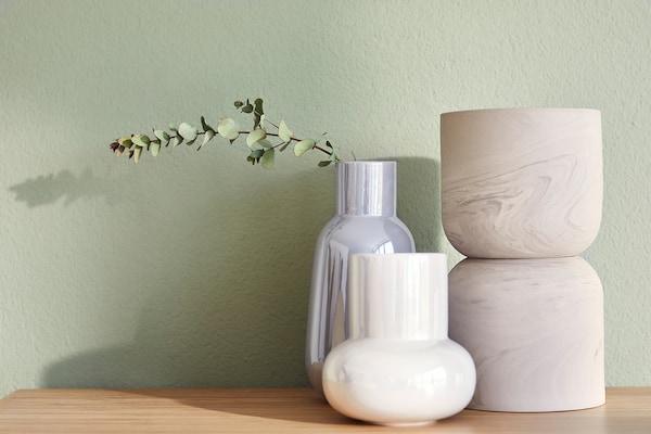 Trois vases posés sur une surface en bambou sur un fond vert clair.