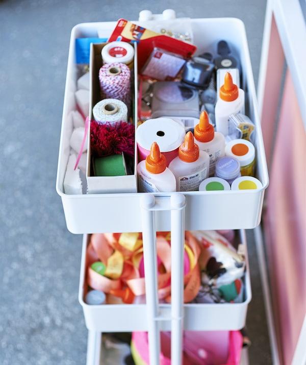 Trójpoziomowy biały wózek wypełniony materiałami plastycznymi takimi jak wstążki, sznurek i klej.