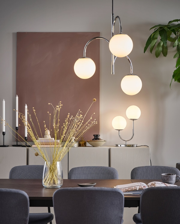 Trójramienna chromowana lampa SIMRISHAMN wisząca nad stołem jadalnianym i lampa stołowa SIMRISHAMN ustawiona na szafce.