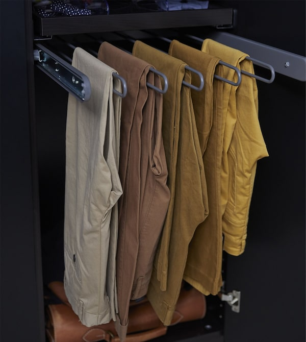 Trousers hang from a KOMPLEMENT pull-out trouser hanger in an IKEA PAX wardrobe.