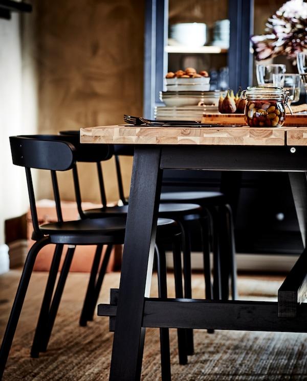 Trpezarijski sto u crnoj/nijansi bagrema, stolice u boji antracita i tepih od jute. Vitrina u pozadini.