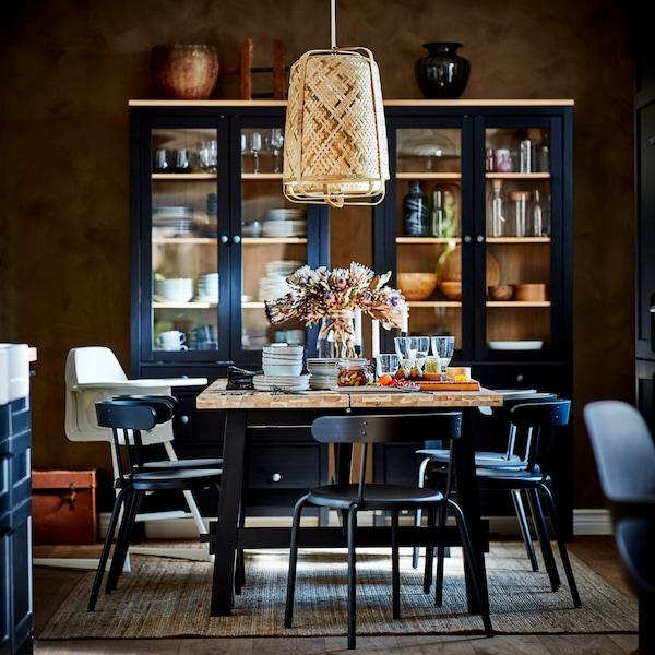Trpezarijski sto u crnoj/nijansi bagrema, stolice u boji antracita, tepih od jute, visilice od bambusa i dva ormarića od pune borovine.