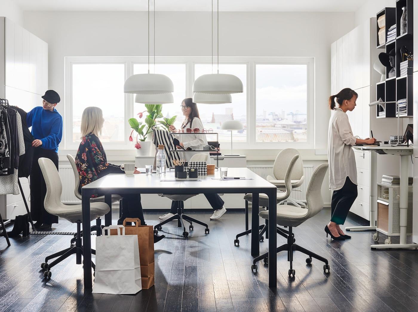 ترتيبات مكتب أبيض معاصر بما في ذلك مكاتب الجلوس-الوقوفBEKANT بيضاء اللون ووحدات تنظيم الرفوف السوداء.