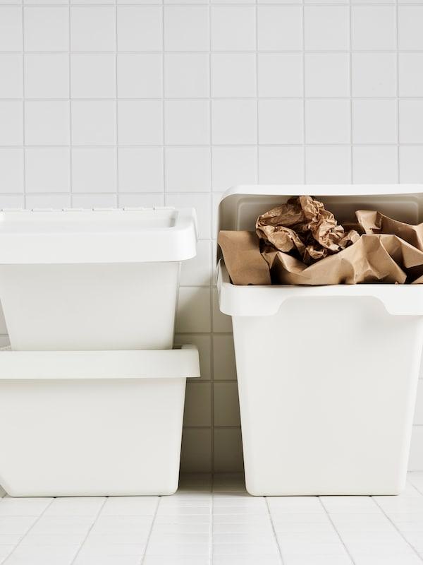 Trzy białe kosze do segregowania odpadów SORTERA, w tym jeden wypełniony zużytym papierem pakowym, ustawione w wyłożonym białymi płytkami ceramicznymi pomieszczeniu.