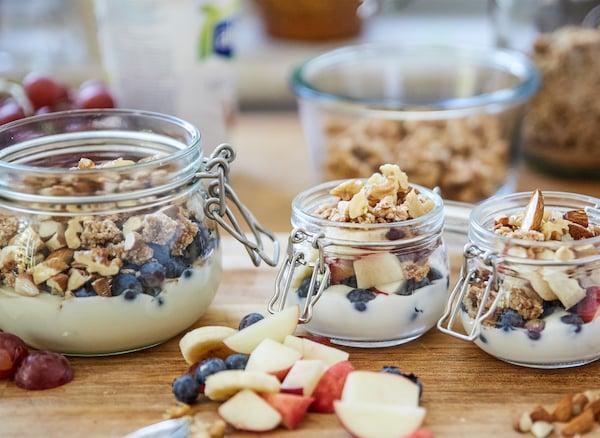 Trzy szklane słoiki wypełnione jogurtem, granolą, świeżymi owocami i orzechami na drewnianym blacie.