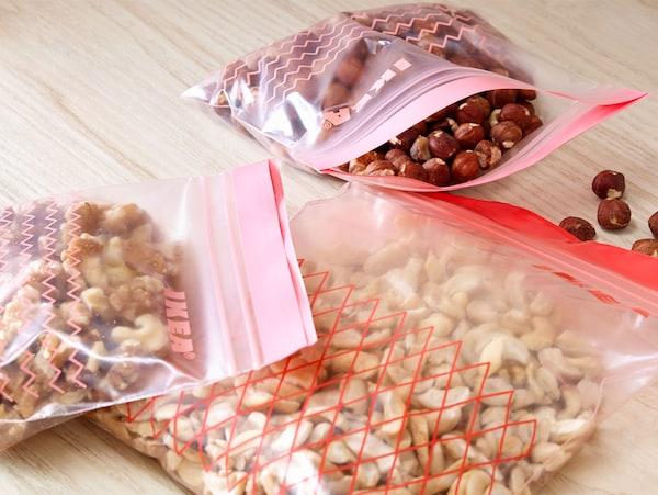 Trzy torebki strunowe ISTAD z różnymi rodzajami orzechów na drewnianym blacie.