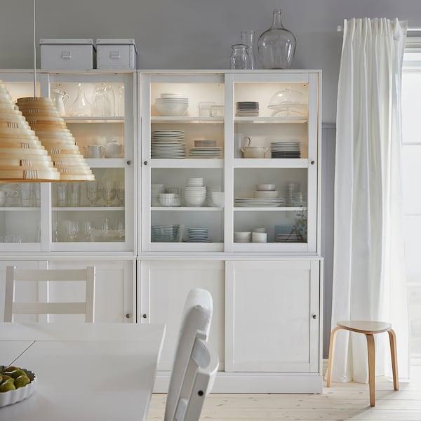 تشكيلة تخزين HAVSTA بيضاء مع أبواب زجاجية انزلاقية بداخلها أواني الطعام وكؤوس في غرفة الطعام.