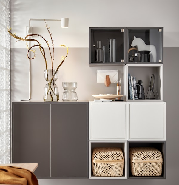 تشكيلة وحدة تخزين EKET أبيض ورمادي مع صندوقي تخزين SMARRA، ومزهريتن زجاجيتين وأغراض شخصية معروضة.