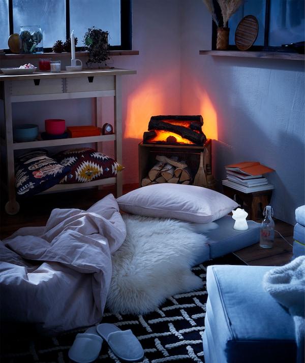 تصميم داخلي نمط كوخ مع موقد صُوري ومراتب على الأرض كسرير مؤقت، بجانهبا أضواء ليل LED.