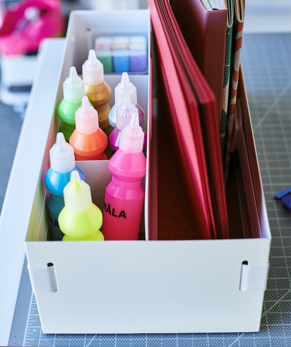 Tubes of colorful paint and notebooks stored in a white desk organizer.