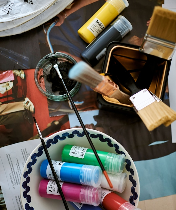 Tubes of coloured paints in a white bowl and paint brushes in a black and gold tin on top of a table covered in newspaper.