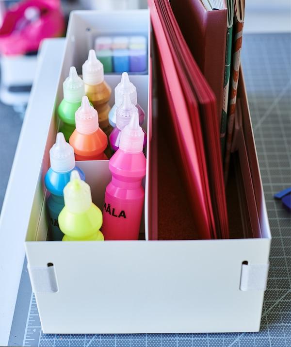 Tubos de pintura de colores y libretas guardados en un organizador de escritorio blanco.