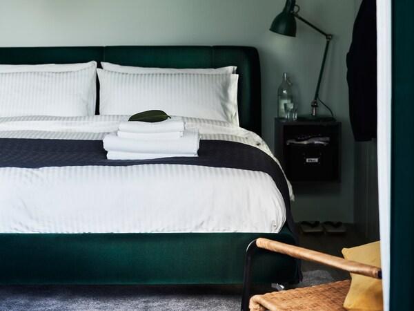 เตียงบุนวม TUFJORD/ทุฟยูร์ด สีเขียวเข้มพร้อมเครื่องนอน NATTJASMIN/นัตต์ยัสมิน ตั้งอยู่้ในห้องนอนตรงผนังสีเขียว