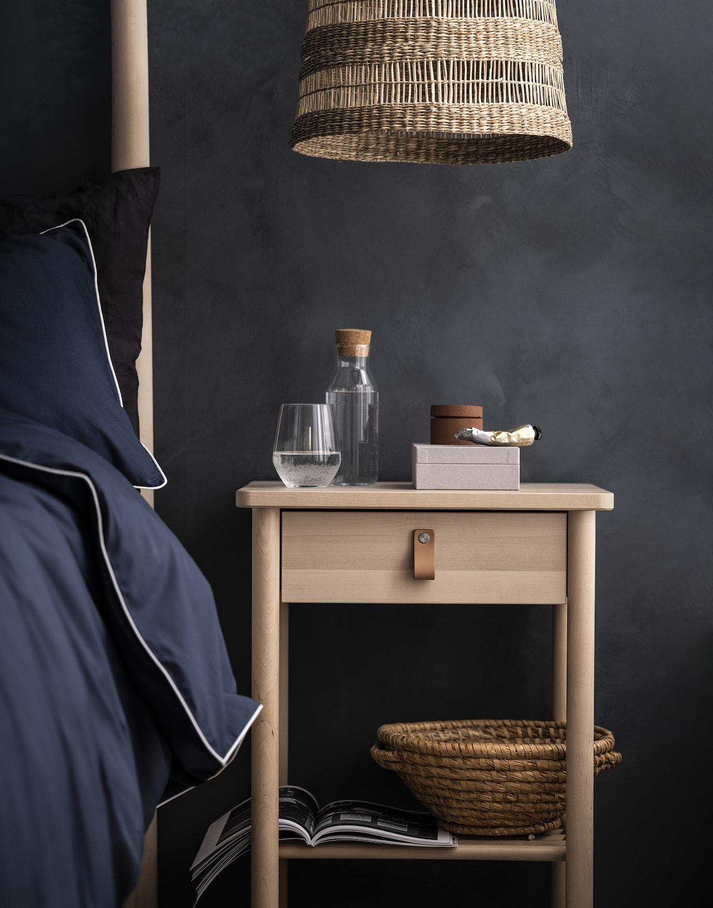 Tummaa seinää vasten puinen yöpöytä, vieressä sänky ja yläpuolella riippuva valaisin.