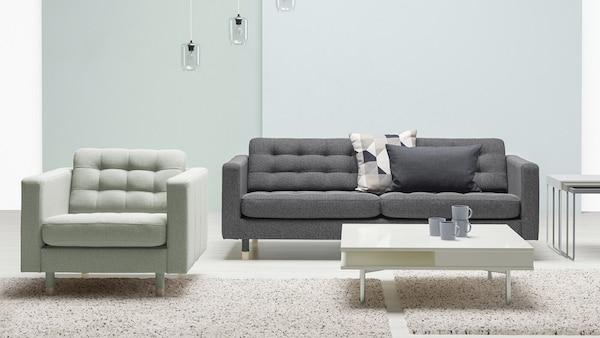 Tummanharmaa LANDSKRONA-sohva jolla on kaksi koristetyynyä. Vieressä vaaleanvihreä LANDSKRONA-nojatuoli. Lattialla kaksi isoa mattoa joiden päällä on vaalea sohvapöytä.