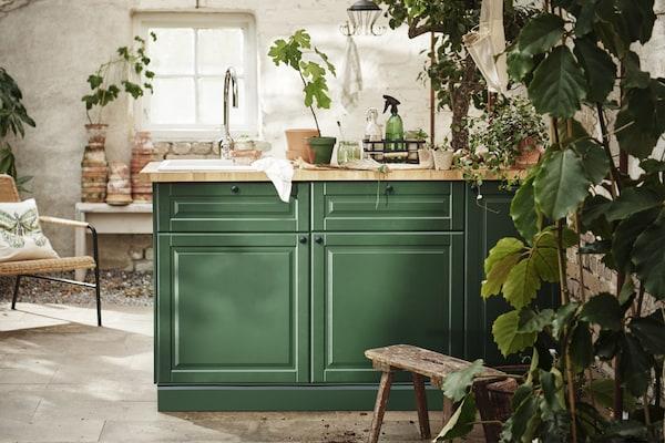 Tummanvihreä keittiö vihreiden kasvien keskellä.