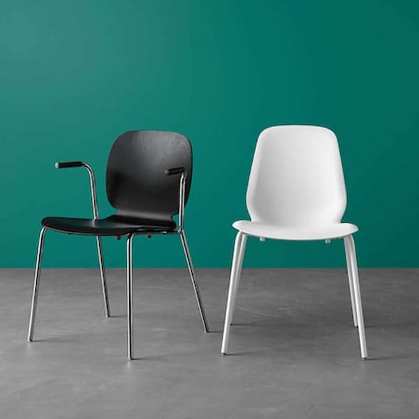 Tummanvihreä seinä jonka edessä on kaksi tuolia, toinen on musta ja toinen on valkoinen.