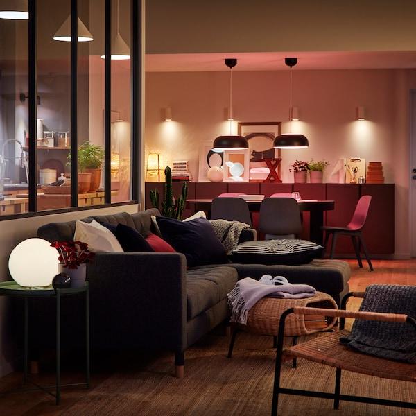 Tunnelmallisesti valaistu avoin olohuone ja keittiötila.