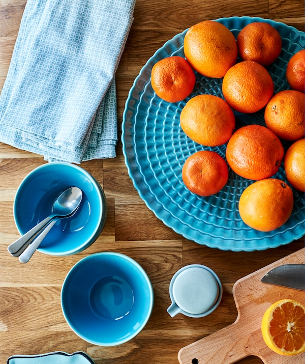 Turquoise teacups, napkins and a serving plate with satsumas on a wooden worktop next to a chopping board and cut satsuma.