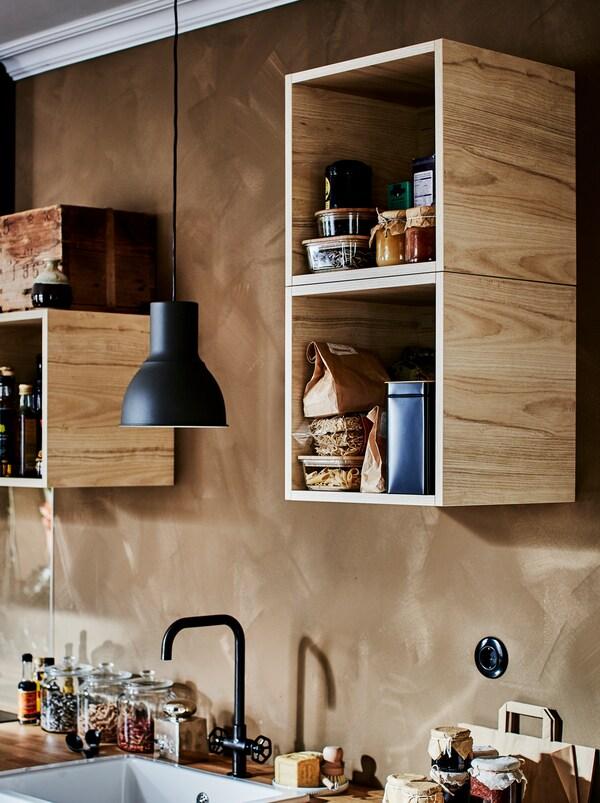TUTEMO ormarići puni različitih kuhinjskih dodataka, neravnomerno raspoređenih duž zida iznad kuhinjskih elemenata.