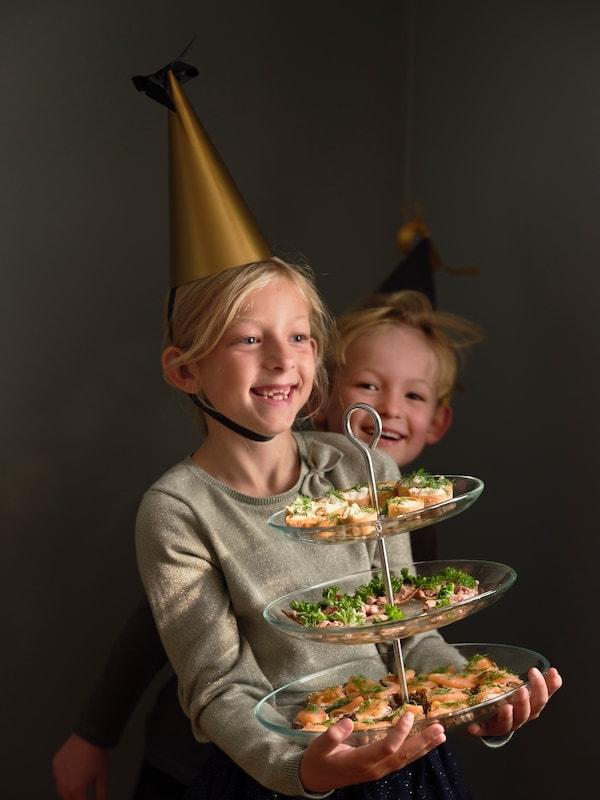 Två barn i partyhattar som bär ett uppläggningsfat med snittar.