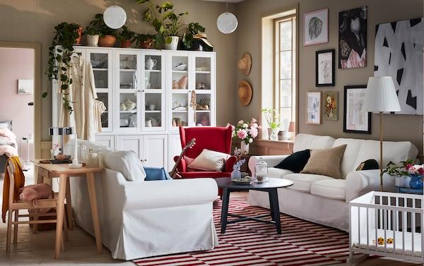 Två EKTORP soffor placerade mittemot varandra i ett modernt, men ändå traditionellt vardagsrum i vitt och rött.