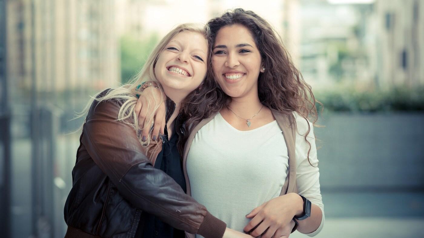 Två glada tjejer som kramas.