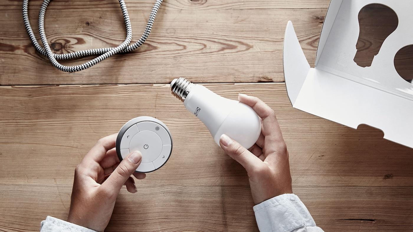 Två händer håller i ett TRÅDFRI set för dimning bestående av en rund fjärrkontroll och en LED-ljuskälla.