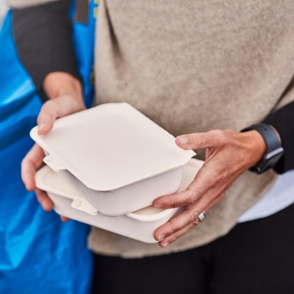 Två händer håller två take-away-lådor.