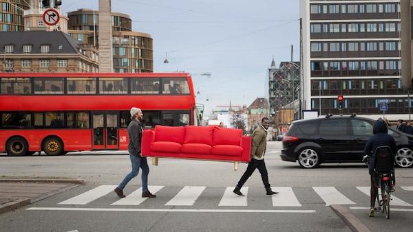 Två män som bär en röd soffa över ett övergångsställe i en stad.