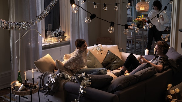 Två personer sitter tillsammans och skrattar och pratar i två soffor som har ställts ihop mitt i ett rum.
