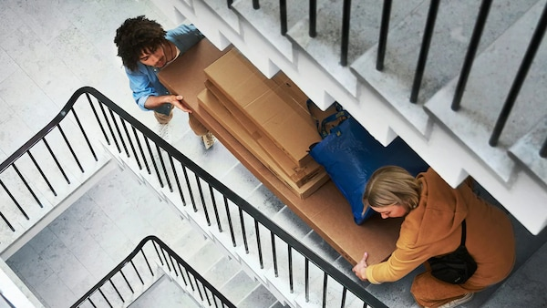 Två personer som bär upp stora kartonger uppför small trappa.