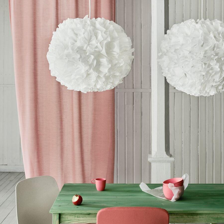 Två VINDKAST taklampor i vit pompomdesign hänger ovanpå ett grönt bord med en rosa gardin i bakgrunden.