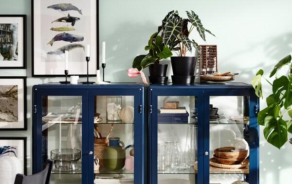 Twee blauwe FABRIKÖR vitrinekasten worden gebruikt om souvenirs uit te stallen. Bovenaan staan planten en kandelaars.