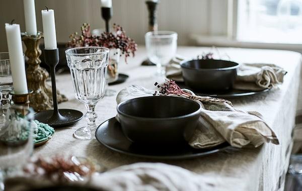 Twee couverts op een linnen tafellaken bestaande uit een grijsblauwe schaal op een bord, met een glazen beker en een geknoopt servet.