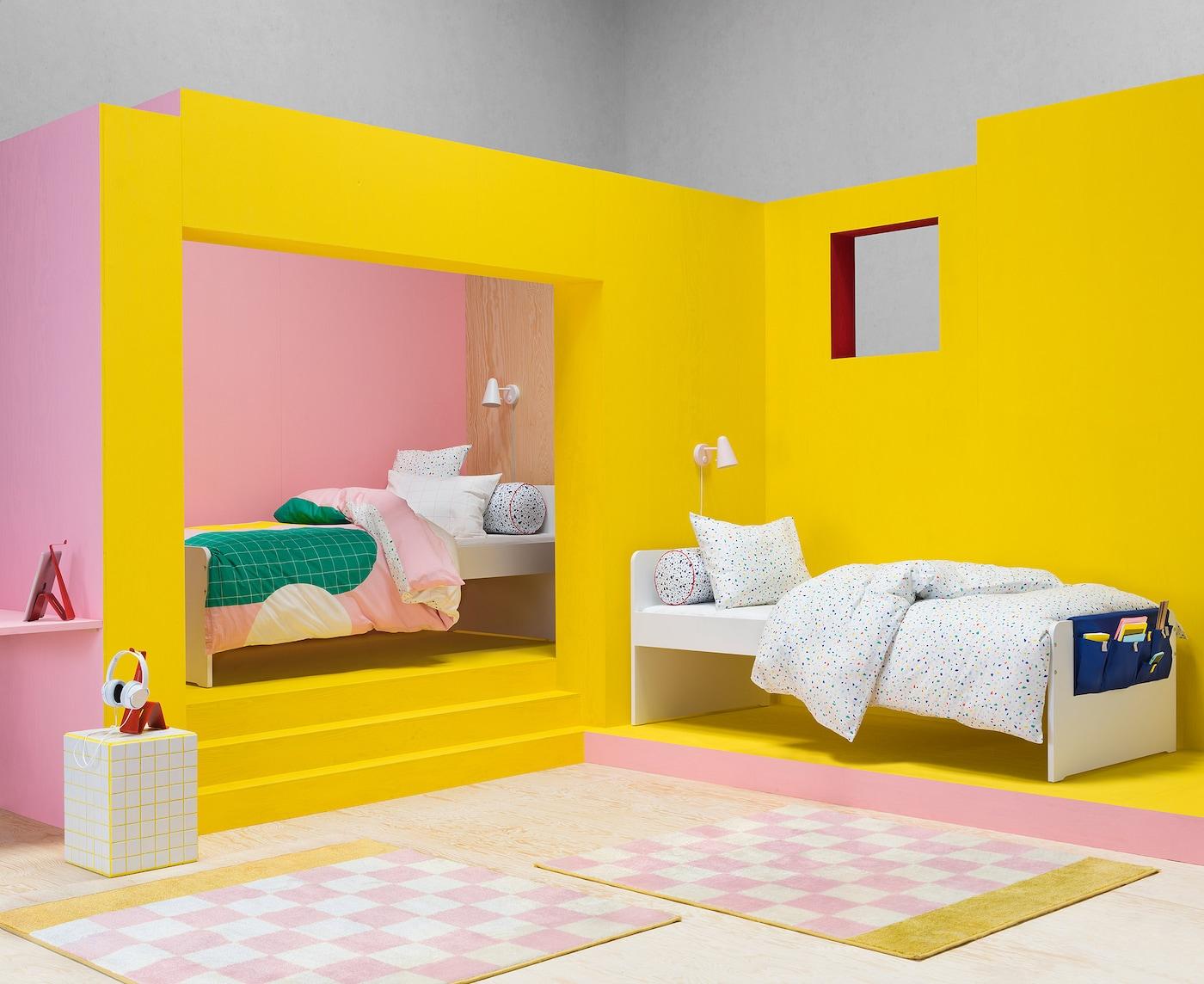 Twee eenpersoonsbedden met MÖJLIGHET overtrekken voor kinderen, in een ruimte met felgele muren en kleurrijke vloerkleden.