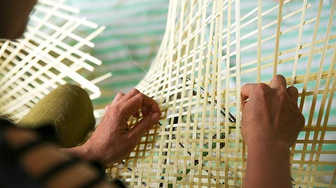 Twee handen die een bamboe mand weven