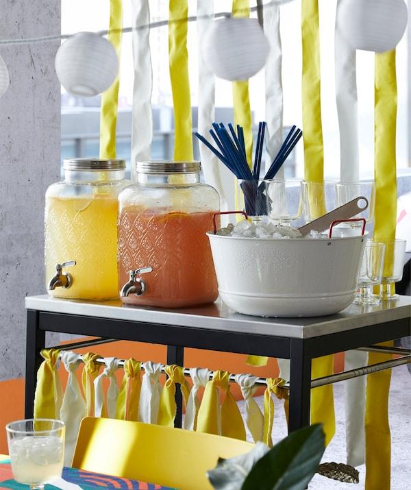 Twee IKEA FÖRFRISKNING glazen vaten met tapkraan in roestvrij staal, gevuld met geel en oranje fruitsap naast een ijsemmer.