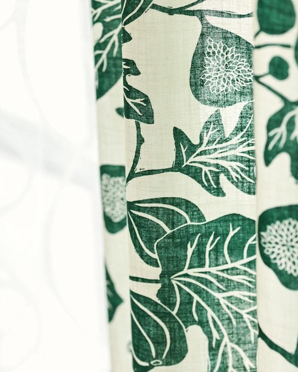 Twee naast elkaar opgehangen stoffen gordijnen, één van dun, wit katoen, één met een grafisch, groen bladpatroon.