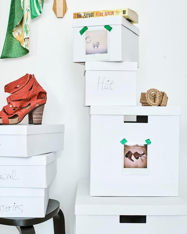 Twee stapels witte dozen. Bovenop één stapel staat een rode schoen. Elke doos draagt een label met woorden of een foto van schoenen.