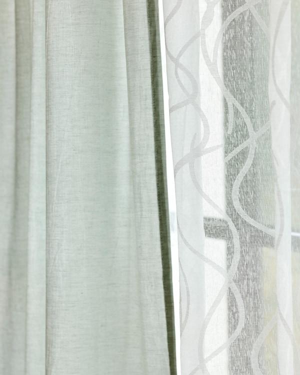 Twee stoffen gordijnen hangen naast elkaar, één in wit doorzichtig katoen en één in lichtgroen linnen.
