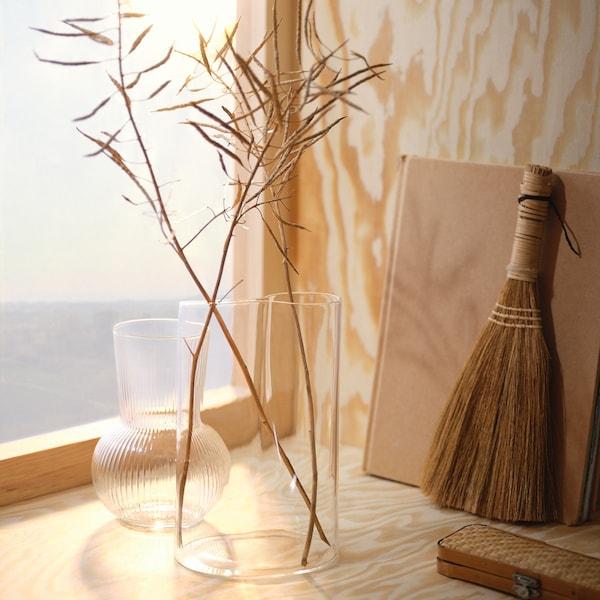 twee transparante vazen met wat takjes in een dennenhouten vensternis met een boekje en een borsteltje ernaast.