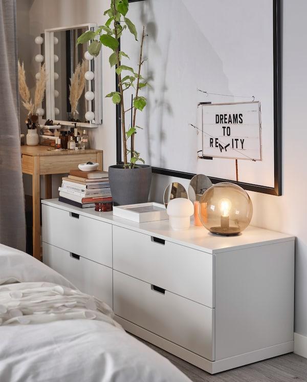 Twee witte NORDLI ladekasten staan naast een wand. Op de ladekasten staan tafellampen, boeken en decoratieve stukken.