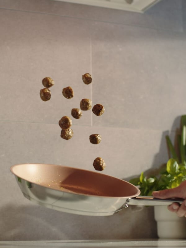 Twelve, HUVUDROLL plant balls suspended in mid-air above a shiny, stainless-steel, frying pan in front of a beige wall.