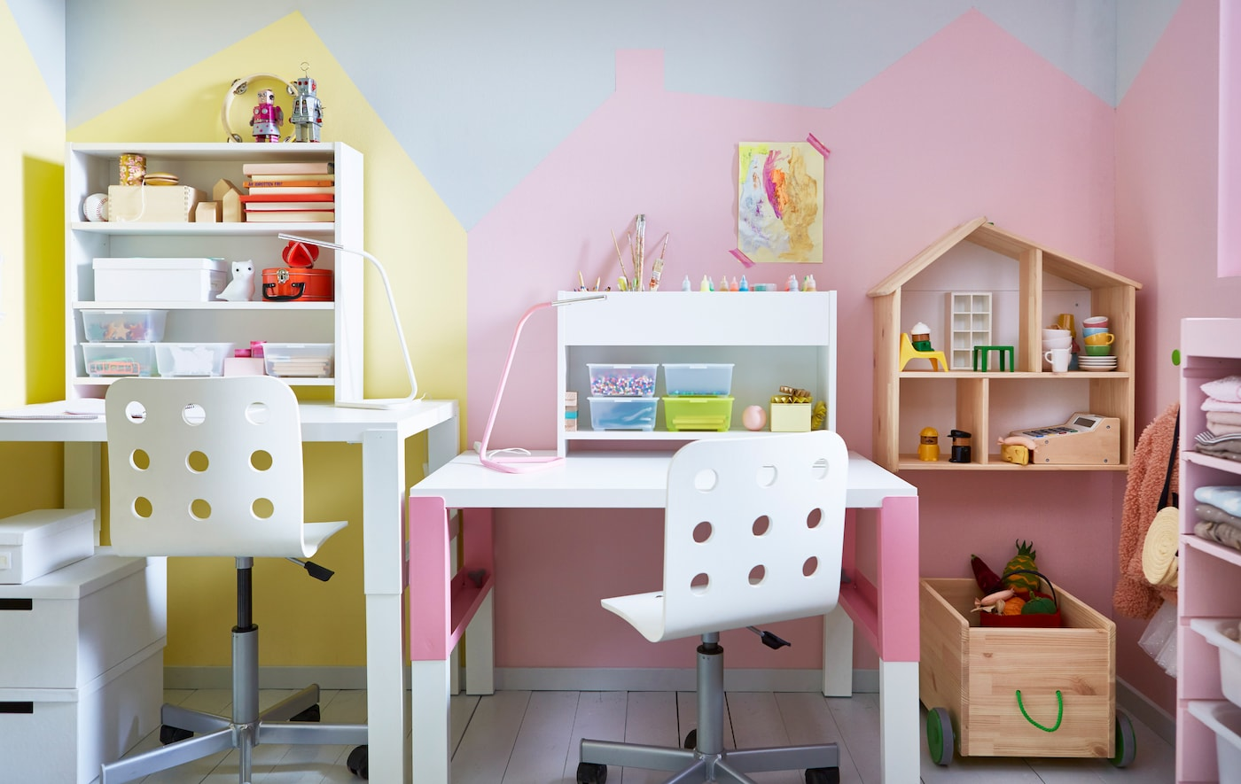 Two adjustable desks and chairs side-by-side in a shared kids' room, with some storage units and a dolls house.