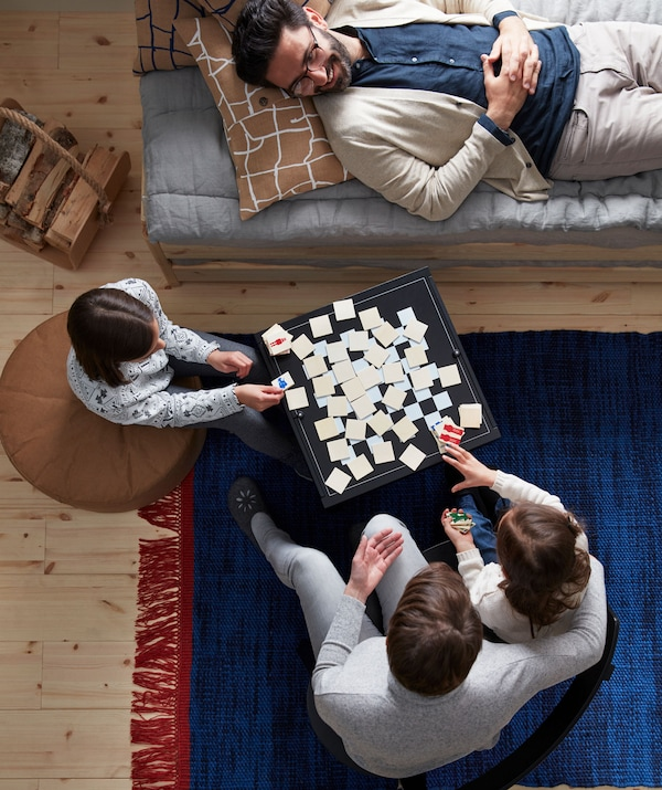 Two adults and two children seated or lying around a game being played on a combined coffee table and board game at centre.